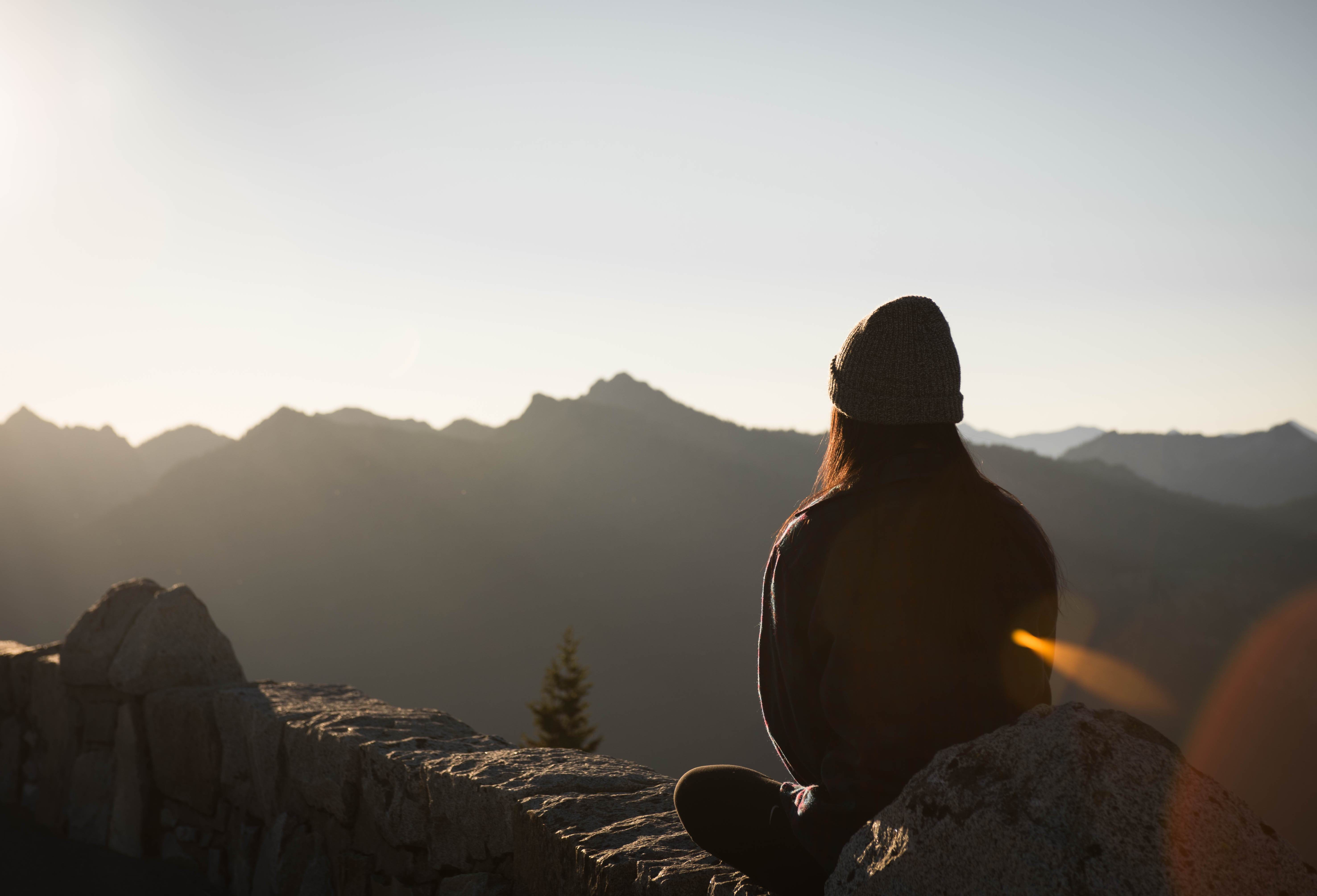 photo-of-a-woman-sat-on-a-mountain-thinking